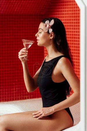 Photo pour Vue de côté de jeune femme détendue avec la fleur dans le martini potable de cheveux avec les yeux fermés dans le centre de spa - image libre de droit