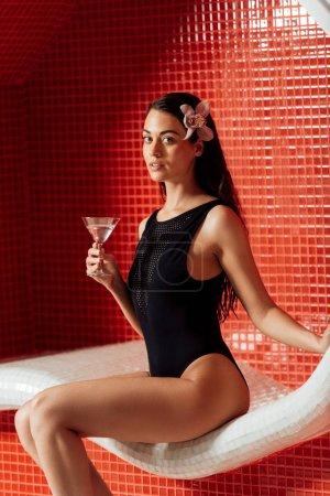 Photo pour Belle femme avec la fleur dans le verre de fixation de cheveux de martini dans le centre de spa - image libre de droit