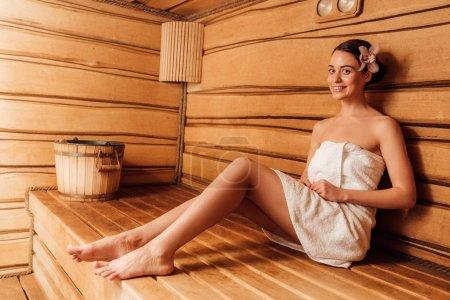 Photo pour Fille nu-pieds de sourire dans la serviette avec la fleur dans le cheveu dans le sauna - image libre de droit