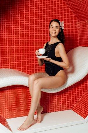 Photo pour Femme nu-pieds souriant retenant la cuvette de café dans le centre de spa - image libre de droit