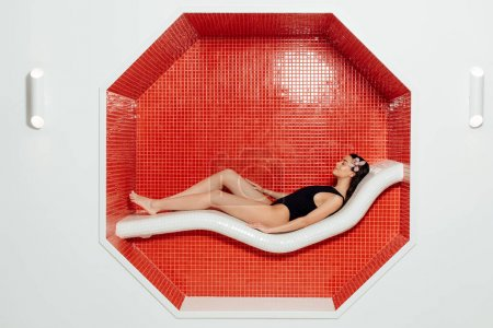 Photo for Side view of attractive young woman in swimsuit lying in spa center - Royalty Free Image