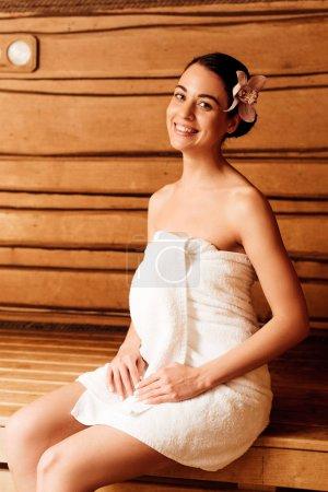 Photo pour Fille de sourire avec la fleur dans le cheveu regardant l'appareil-photo dans le sauna - image libre de droit