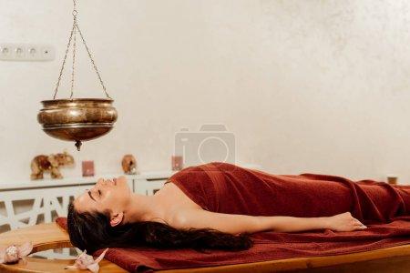 Photo pour Vue latérale de la femme se trouvant sous le bateau de shirodhara pendant la procédure ayurvédique - image libre de droit