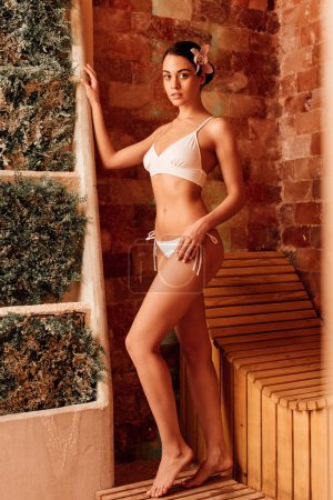 Photo for Full length view of slim woman in swimsuit in sauna - Royalty Free Image
