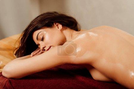 Photo pour Jeune femme détendue couchée les yeux fermés sur une table de massage - image libre de droit