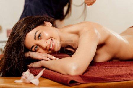 mujer sonriente disfrutando de masaje ayurvédico en el centro de spa