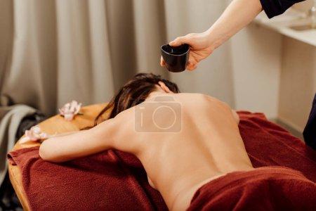 Photo pour Vue recadrée de masseur faisant massage ayurvédique dans le centre de spa - image libre de droit