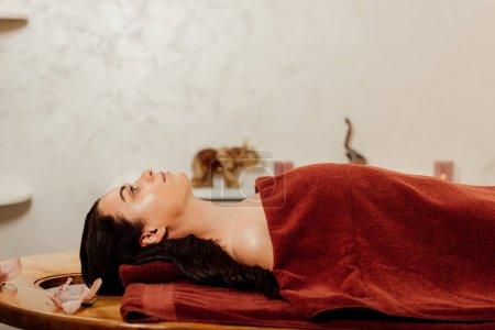 Photo pour Vue de côté de femme se trouvant sous la serviette sur la table de massage - image libre de droit