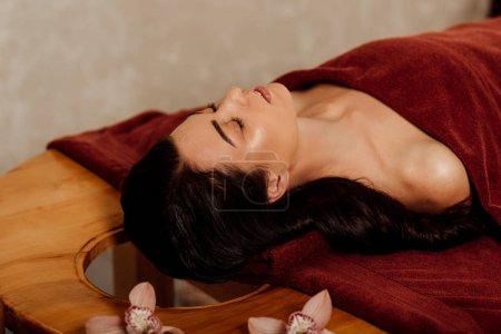 Photo pour Femme détendue couchée les yeux fermés sous la serviette sur la table de massage - image libre de droit