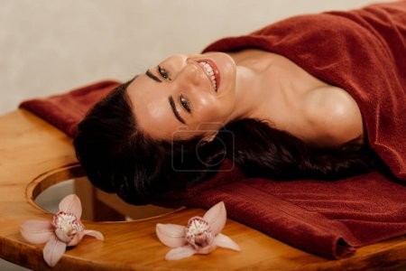 Photo for Smiling young woman lying under towel on massage table - Royalty Free Image