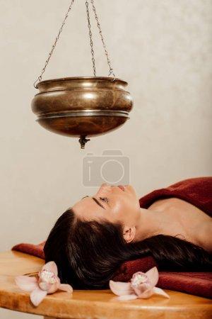 Photo pour Jeune femme détendue se trouvant sous le bateau de shirodhara pendant la procédure ayurvédique - image libre de droit
