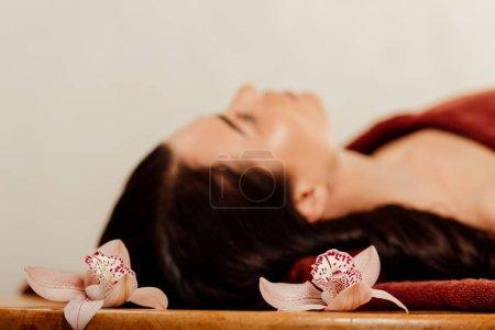 Photo pour Foyer sélectif de la femme se trouvant sur la table de massage avec des fleurs - image libre de droit