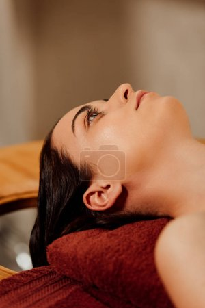 Photo pour Young woman lying on massage table in spa center - image libre de droit