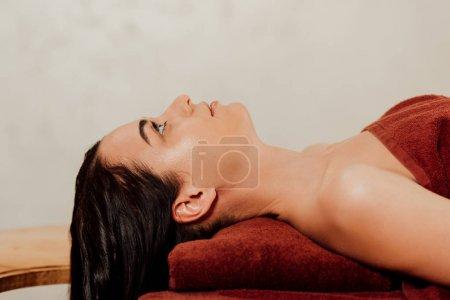 Photo pour Vue latérale de la jolie femme détendue allongée sur une table de massage - image libre de droit