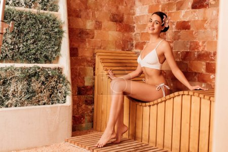 Photo pour Young woman in white bikini on wooden bench in spa center - image libre de droit
