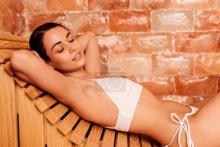 Photo for Relaxed woman in swimsuit lying on wooden bench with closed eyes - Royalty Free Image