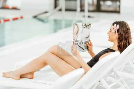 Photo pour Young woman reading magazine on sunbed in spa center - image libre de droit