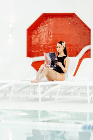 Photo for Young woman reading magazine on sunbed in spa center - Royalty Free Image