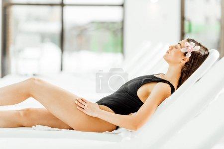 Photo pour Vue latérale de jolie jeune femme se trouvant sur le lit de soleil dans le centre de spa - image libre de droit