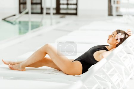 Photo for Pretty young woman lying on sunbed in spa center - Royalty Free Image