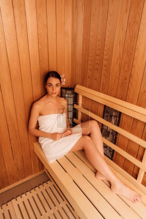 Foto de Vista de ángulo alto de la mujer en la toalla en la sauna - Imagen libre de derechos