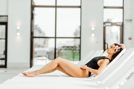 Photo pour Pretty young woman lying on sunbed in spa center - image libre de droit