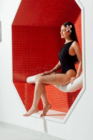 Photo for Smiling young woman in swimsuit sitting on sofa in spa center - Royalty Free Image