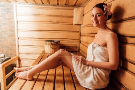 Photo pour Femme de sourire dans la serviette avec la fleur dans le cheveu dans le sauna - image libre de droit