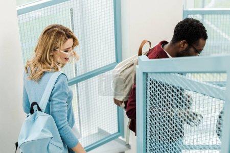 Photo pour Étudiants multiculturels souriants avec des sacs à dos sur des escaliers à l'université - image libre de droit
