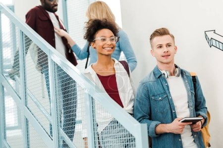 Photo for Four smiling multiethnic students with backpacks on stairs - Royalty Free Image
