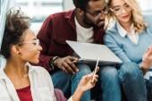 """Постер, картина, фотообои """"three smiling multiethnic students using laptop and smartphone in college"""""""