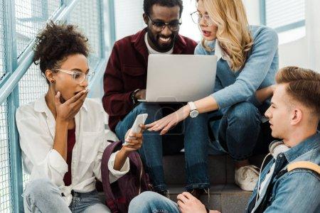Photo pour Groupe d'étudiants multiculturels surpris avec ordinateur portable et smartphone à l'université - image libre de droit