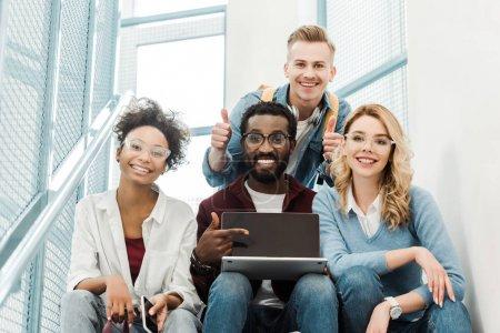 Photo pour Groupe d'étudiants multiculturels de sourire avec l'ordinateur portatif affichant des pouces vers le haut dans l'université - image libre de droit