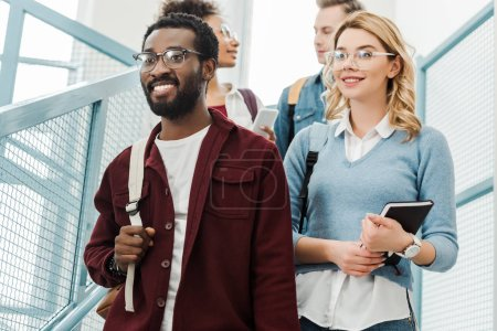 Foto de Group of multiethnic students with backpacks in college - Imagen libre de derechos