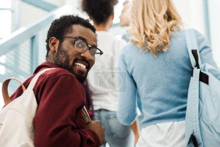 Photo pour Étudiant américain africain de sourire dans des glaces avec le sac à dos regardant l'appareil-photo - image libre de droit