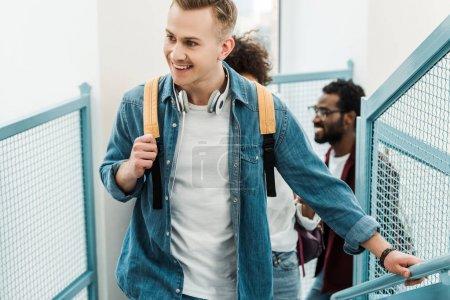 Photo pour Étudiants multiethniques souriants avec des sacs à dos sur des escaliers dans l'université - image libre de droit