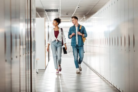 Photo for Full length view of two multiethnic students in corridor in university - Royalty Free Image
