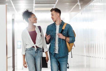 Foto de Two multiethnic students looking at each other in corridor in university - Imagen libre de derechos
