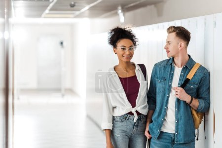 Photo for Two multiethnic students standing in corridor in university - Royalty Free Image