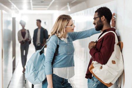 Photo pour Étudiants multiethniques souriants restant dans le couloir dans l'université - image libre de droit