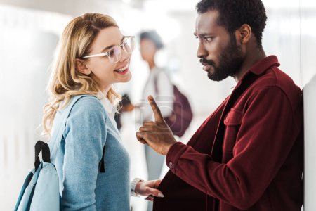 Photo for Two multicultural students looking at each other in college - Royalty Free Image