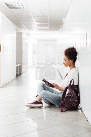 Photo pour Vue latérale de l'étudiant américain africain avec le cahier s'asseyant sur l'étage à l'université - image libre de droit