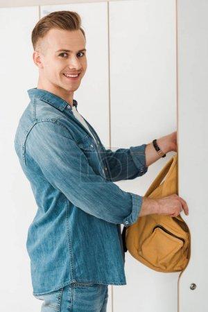 Photo pour Étudiant de sourire mettant le sac à dos dans le casier et regardant l'appareil-photo - image libre de droit