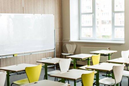 Photo pour Salle de classe avec bureaux en bois, chaises, fenêtre et tableau à feuilles mobiles - image libre de droit