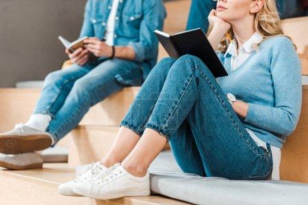Photo pour Vue partielle des étudiants en jeans avec des cahiers dans la salle de conférence - image libre de droit