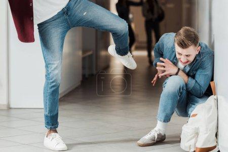Photo pour Vue recadrée de deux étudiants se battant dans le couloir au collège - image libre de droit