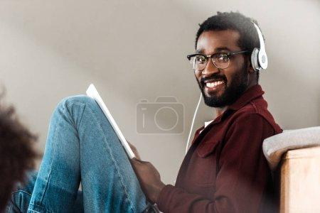 Photo pour Étudiant afro-américain dans le casque utilisant la tablette numérique à l'université - image libre de droit