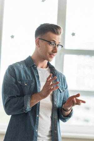 Photo pour Emotional student in glasses and denim shirt gesturing while talking in university - image libre de droit