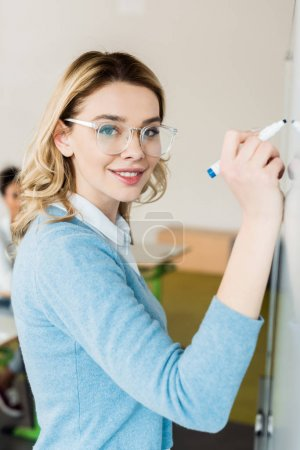 pretty student in glasses writing on flipchart with smile