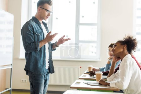 Photo pour Student in glasses and denim shirt standing in front of desks and talking with friends - image libre de droit